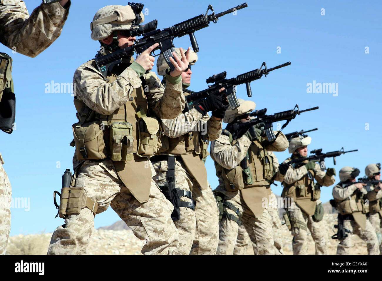 Military Transistion Team members quickly reload their rifles. - Stock Image
