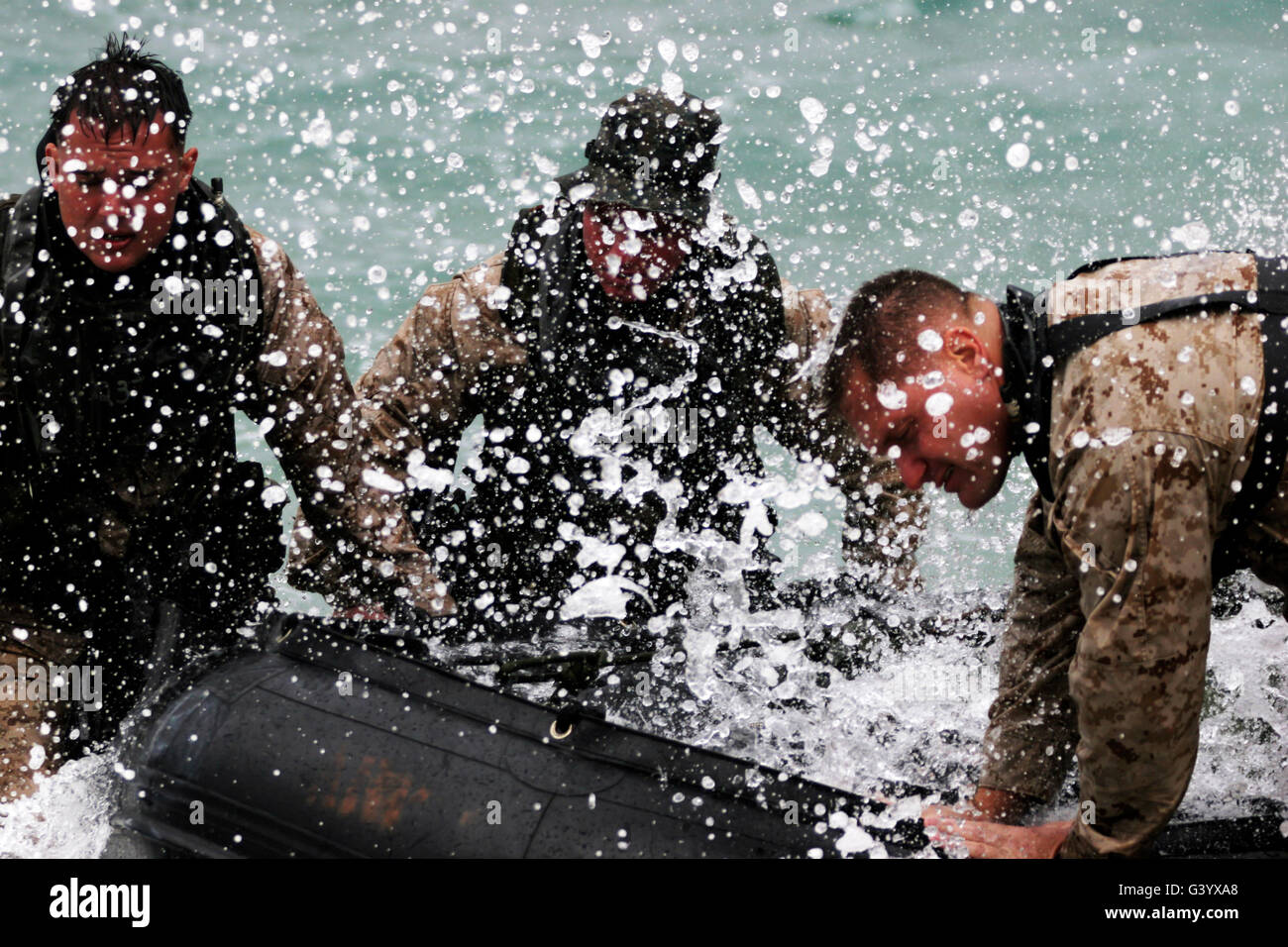 Reconnaissance Marines pull a Zodiac combat rubber reconnaissance craft out of the ocean. - Stock Image