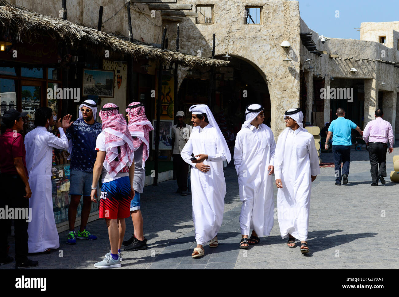 QATAR, Doha, Bazar Souq Waqif , western tourist with arab headgear souvenir and qatari men in traditional white Stock Photo