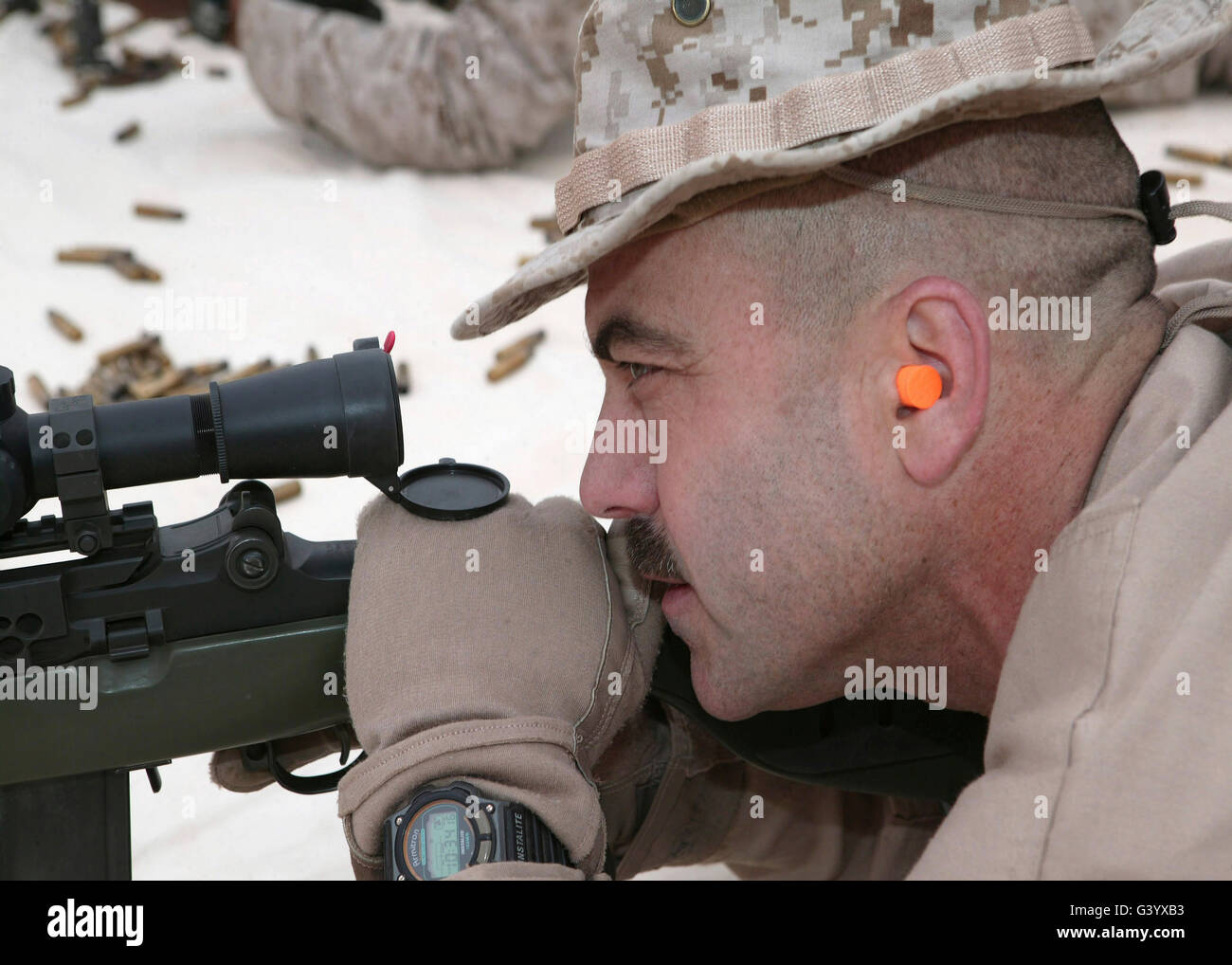 Officer sights in on the target with a Designated Marksmanship Rifle. - Stock Image