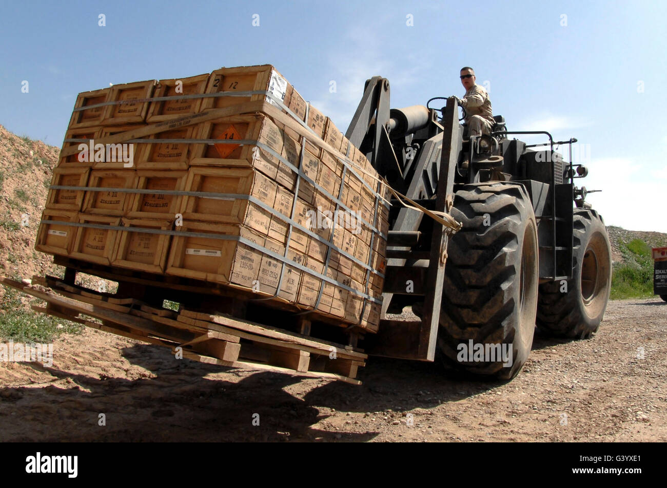 Airman loads a pallet of ammunition onto a truck for delivery. - Stock Image