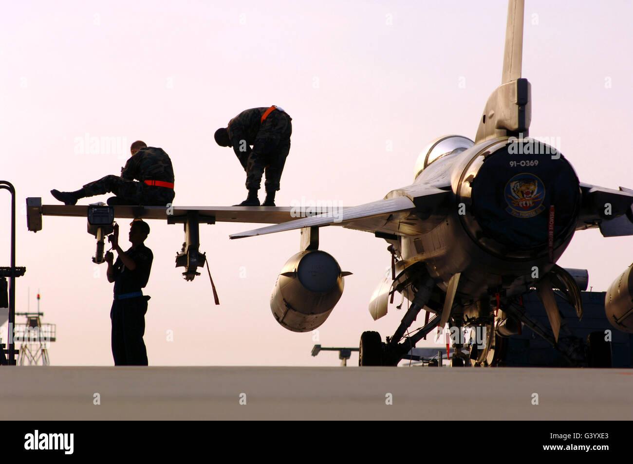 rew chiefs prepare an F-16 Fighting Falcon for take-off. - Stock Image