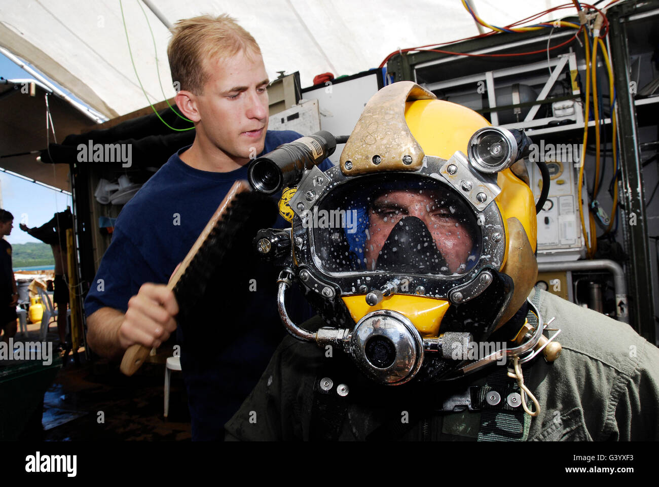 U.S. Navy Diver performs a leak check on a Navy Diver. - Stock Image