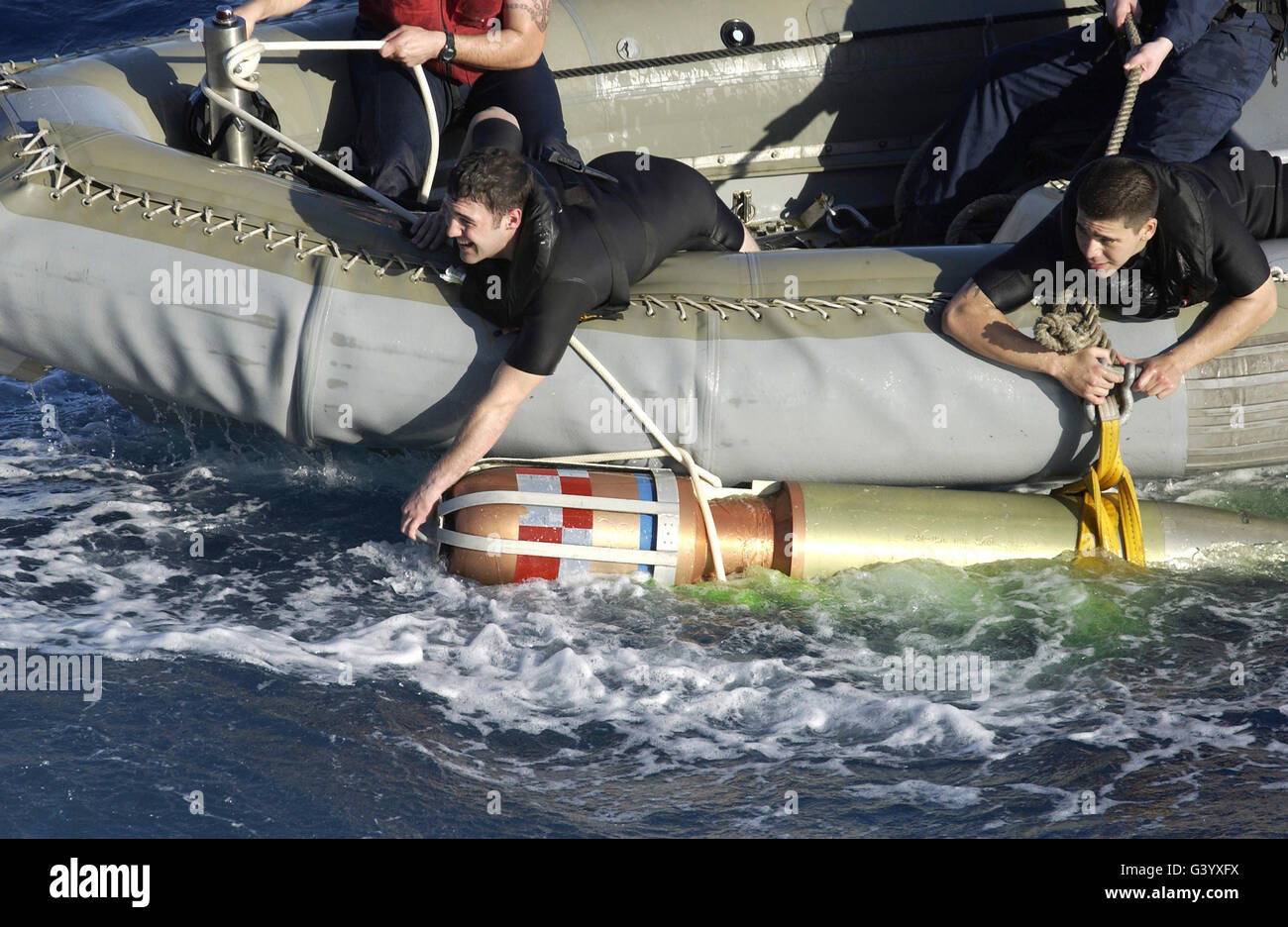 Rescue swimmers pull a 480-pound recoverable exercise torpedo back to the ship. - Stock Image