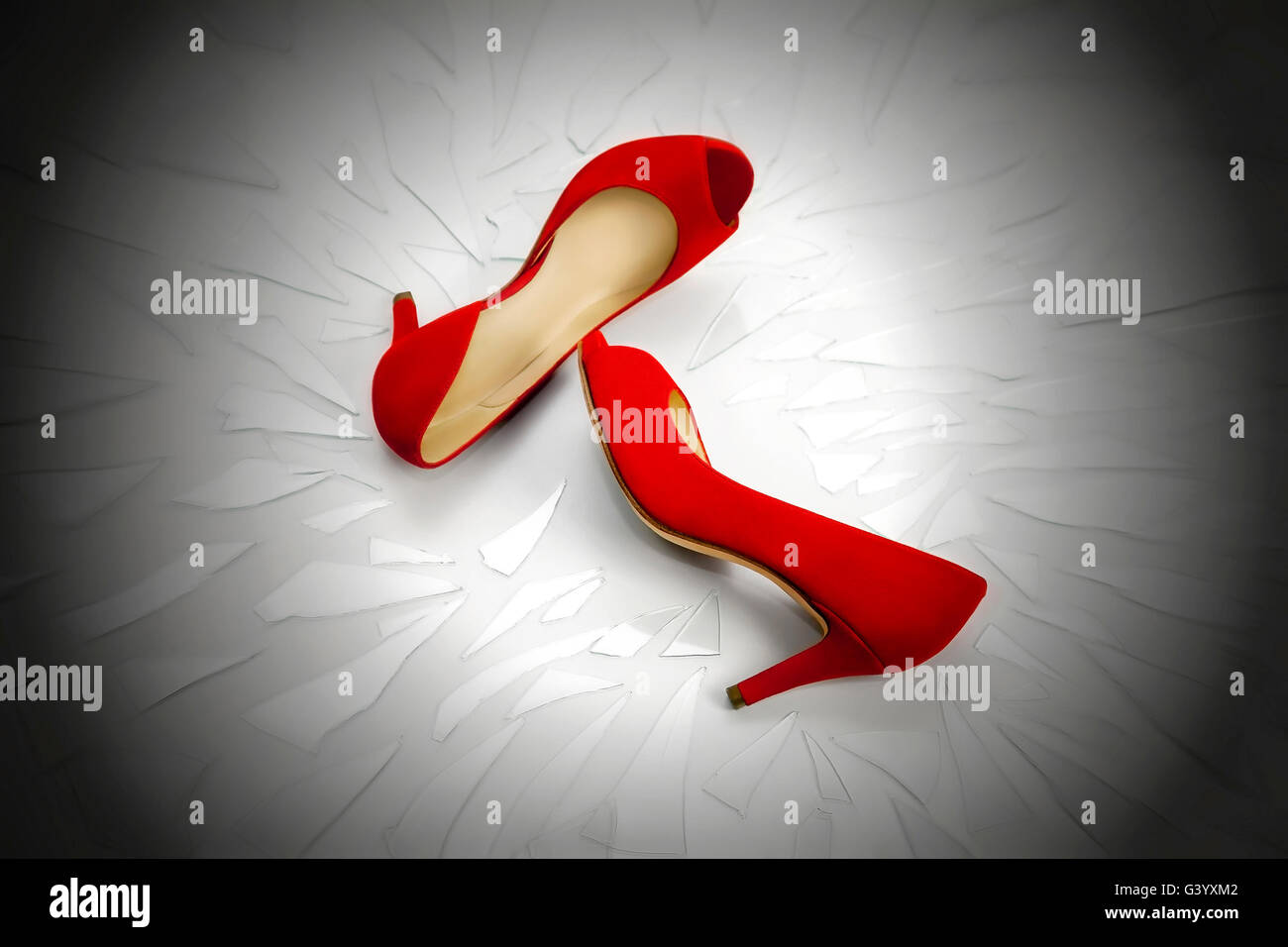 Two women's shoes red, rest on a plan full of broken glass fragments. The image symbolizes the continuing violence - Stock Image