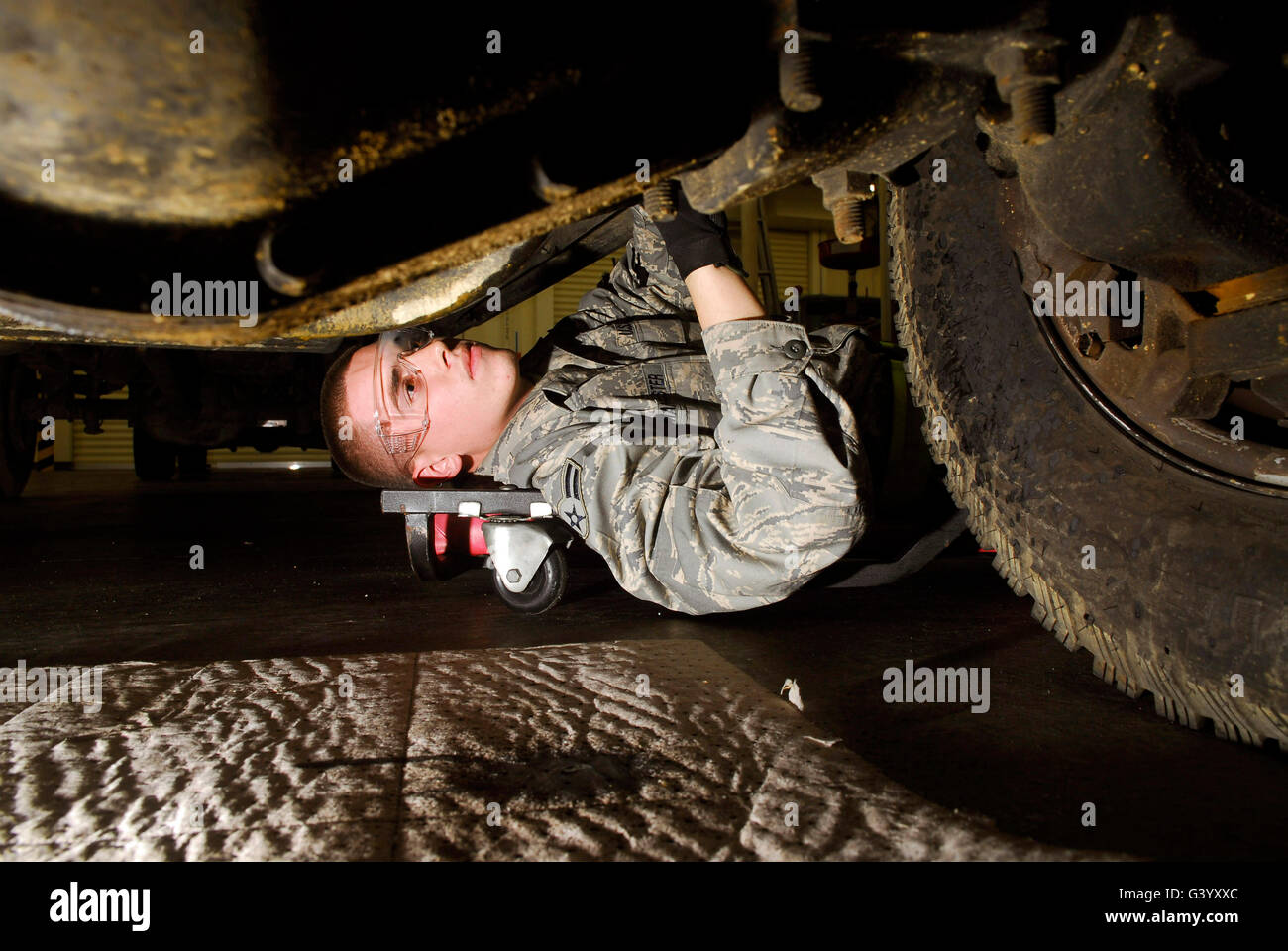 An Airman inspects the undercarriage of an F-350 truck. - Stock Image
