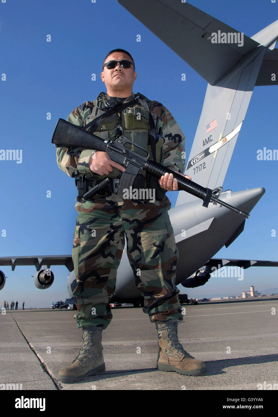A soldier scans stands guard close to the secured perimeter of a C-17 Globemaster III. - Stock Image