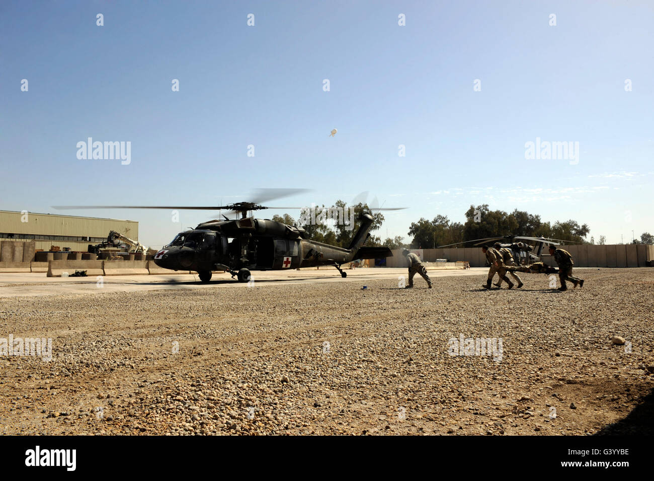 Soldiers rush a simulated casualty to a UH-60 Blackhawk helicopter. - Stock Image