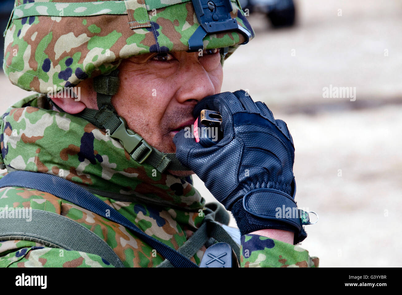 A member of the Japan Ground Self-Defense Force relays instructions to his troops over a radio. - Stock Image