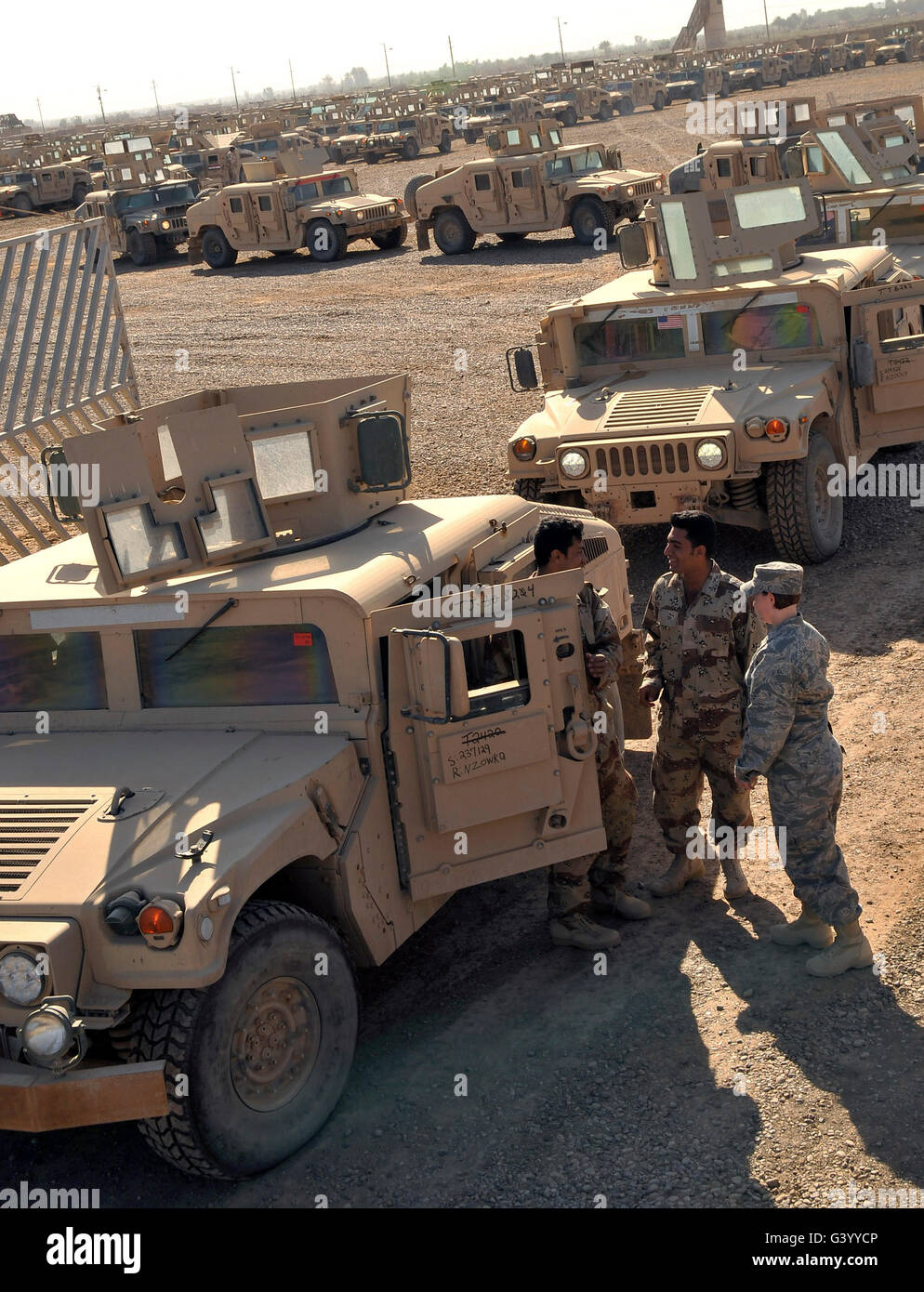 U.S. Army soldier speaks with Iraqi Army Soldiers prior to them driving M1114 HMMWVs. Stock Photo