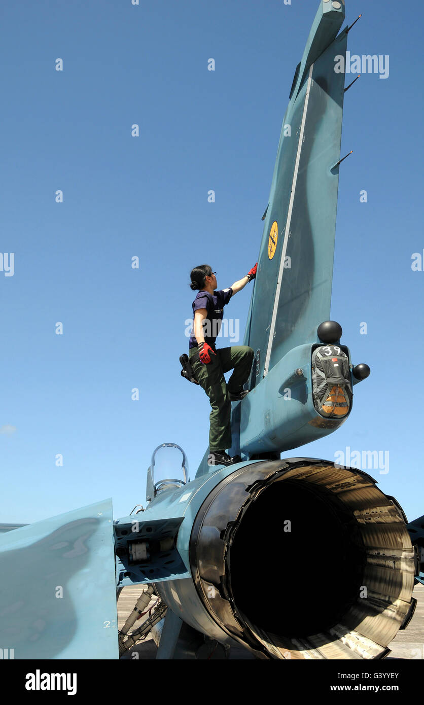 A technician performs post flight maintenance on a JASDF F-2 fighter aircraft. - Stock Image