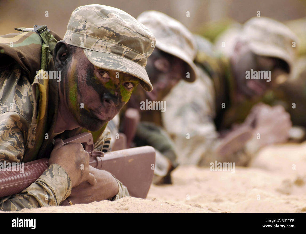 Crawling into the sand, members of team Vandenberg simulate an enemy attack. - Stock Image