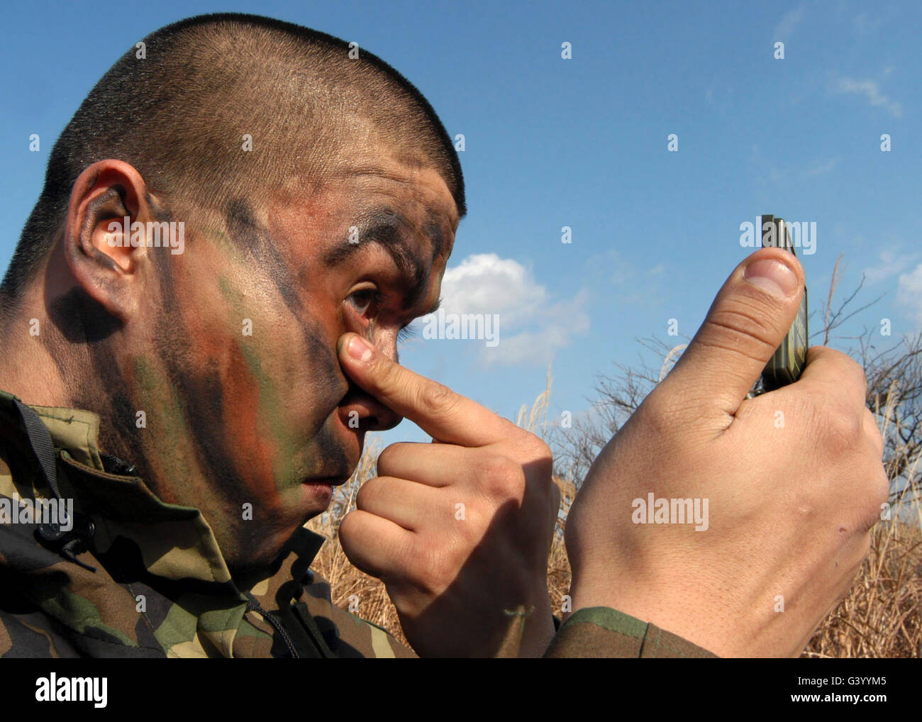 A soldier applying face paint prior to the start of Quarterly Air Base Defense Training, Misawa Air Base, Japan. - Stock Image