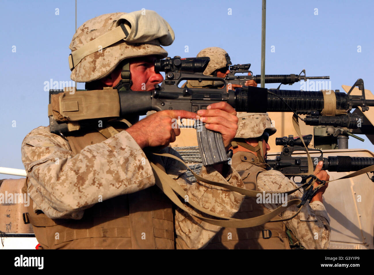 U.S. Marines sighting in on a suspicious group of people in Michigan, Iraq. - Stock Image