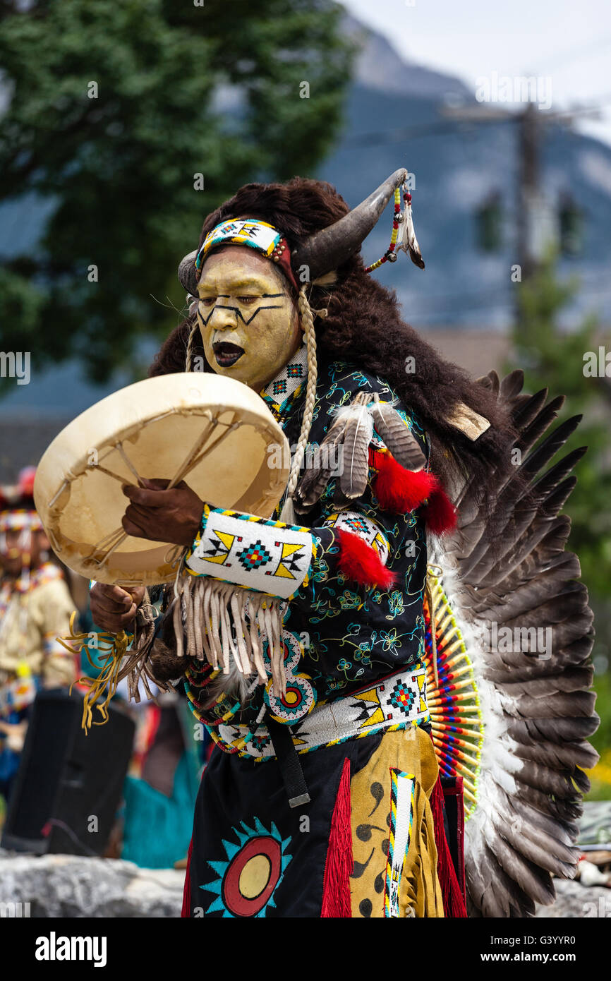 BANFF, CANADA- JUL 3, 2014: A native Blackfoot indian chief wearing a split-horn bonnet dances at a performance - Stock Image