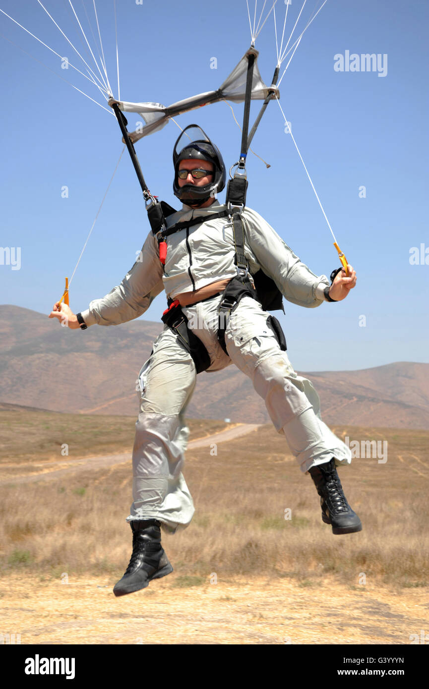 An explosive ordinance disposal technician flaring the canopy of his MT-2XX parachute. - Stock Image