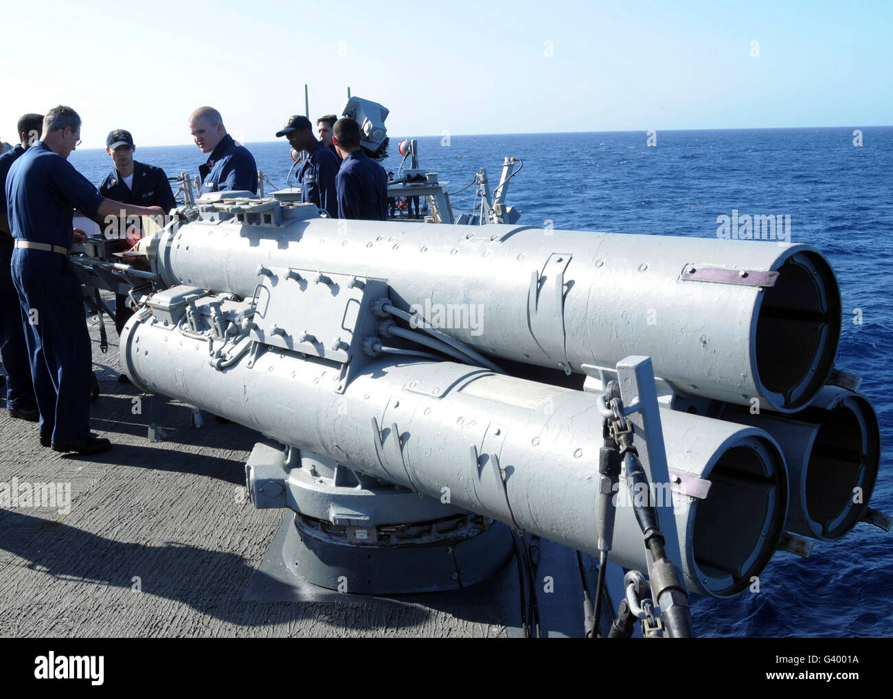 Crew members aboard the guided-missile destroyer USS Porter loading a Mark 46 recoverable exercise torpedo. Stock Photo