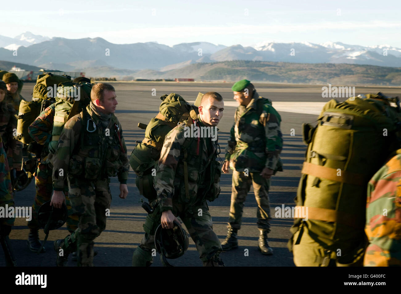 Members of the French Foreign Legion and soldiers from Belgium (with yellow markings in uniforms) walk across the - Stock Image