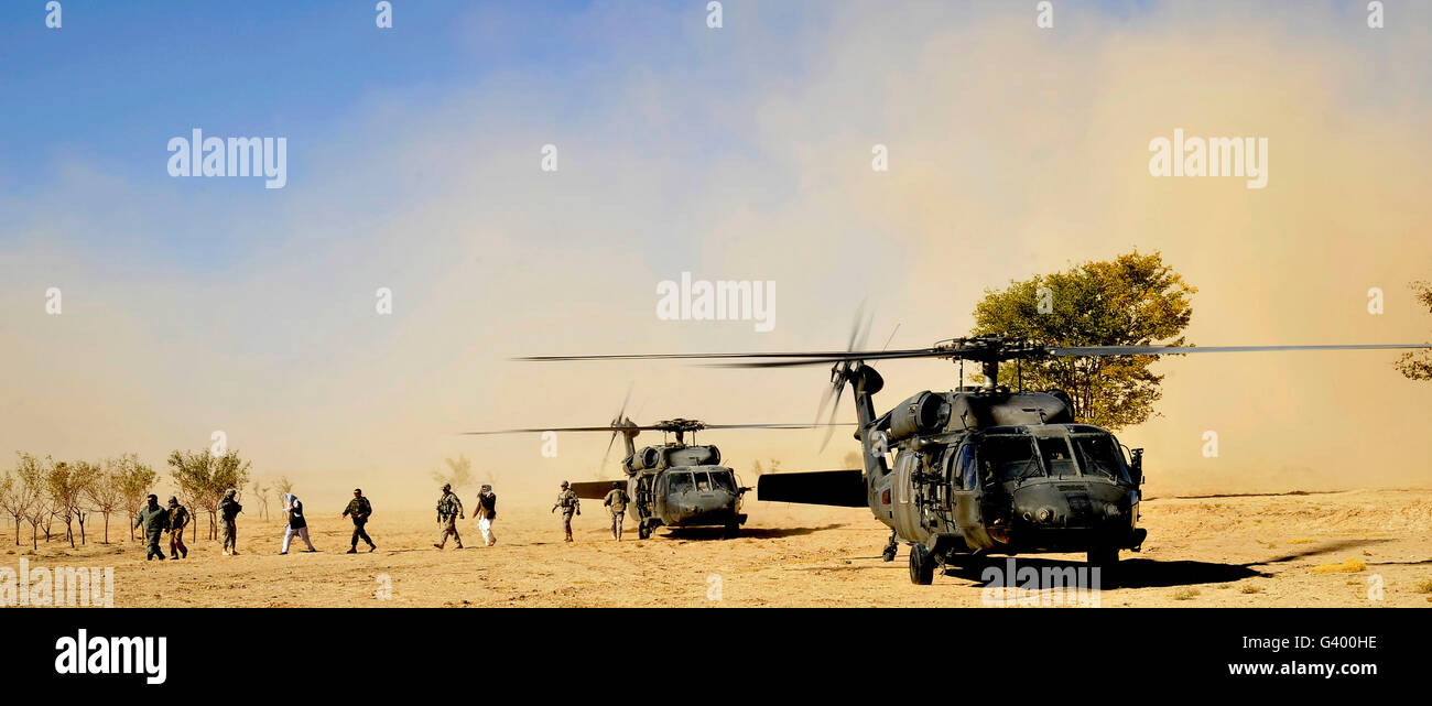 U.S. military members, civilian agencies, and Afghan officials disembark from U.S. helicopters. - Stock Image