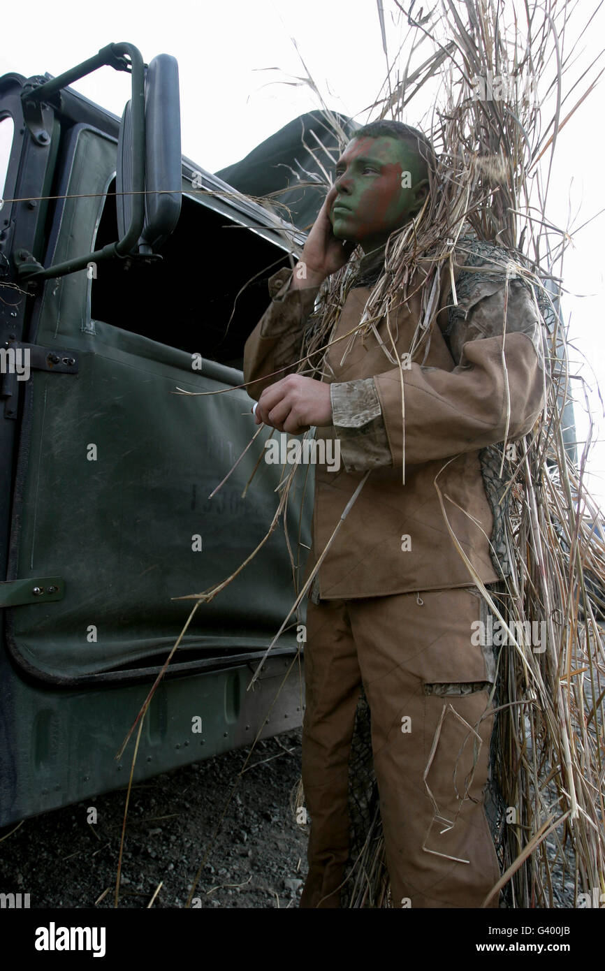 A scout observer applies camouflage paint after donning his homemade ghillie suit. - Stock Image
