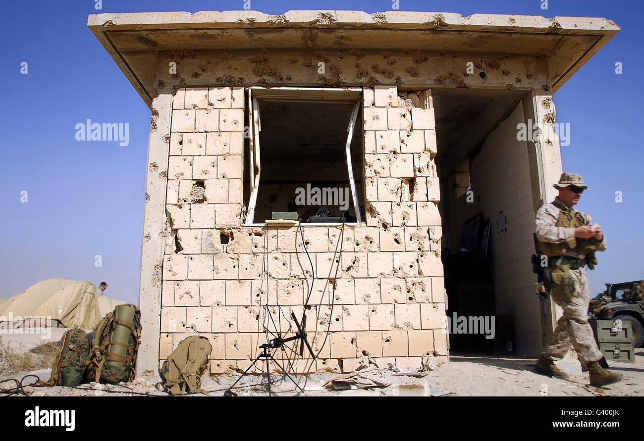 An abandoned structure pocked by bullets serves as an operations center. - Stock Image