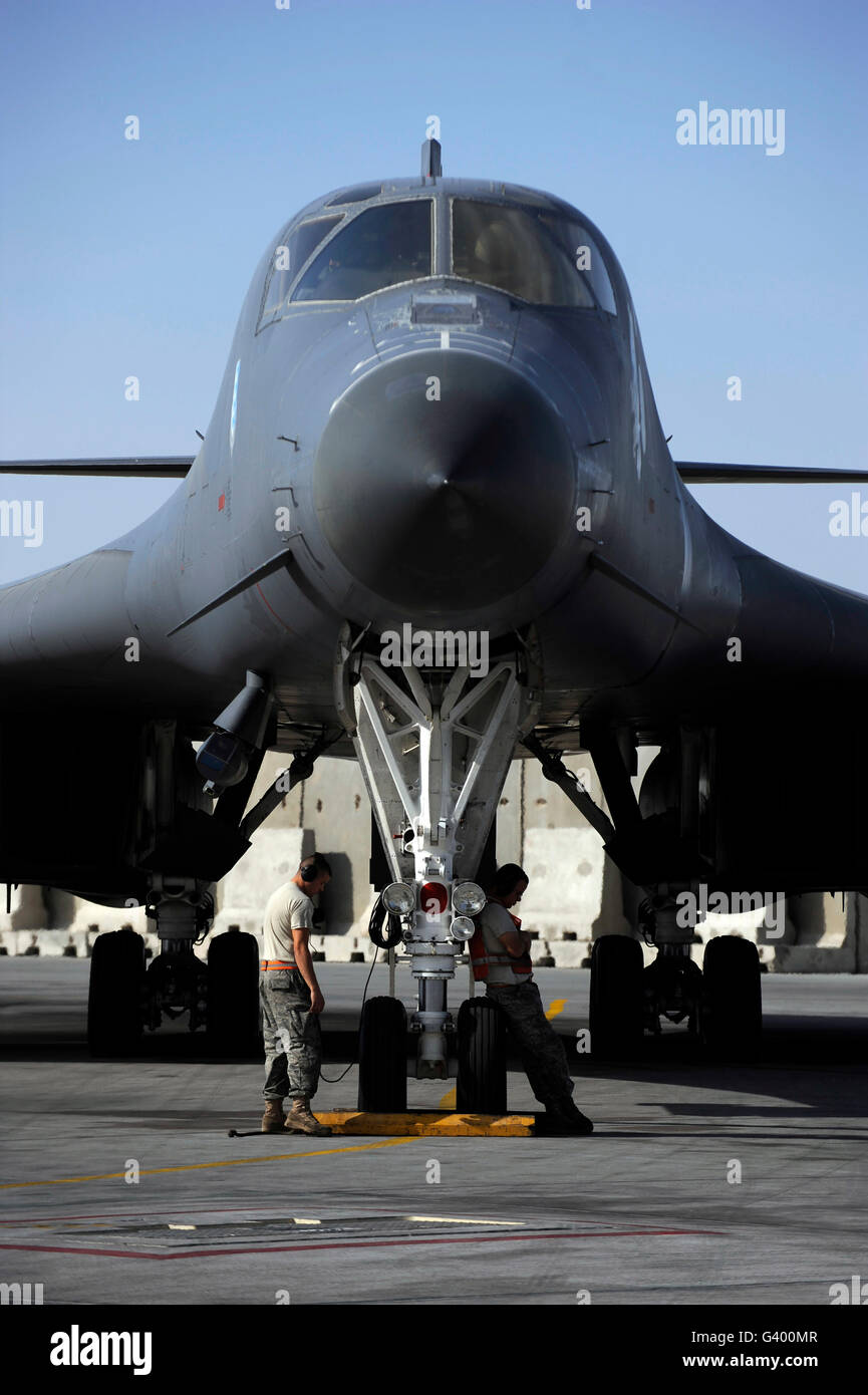 Crew chiefs wait for a B-1B Lancer aircrew to accomplish system checks prior to takeoff. - Stock Image