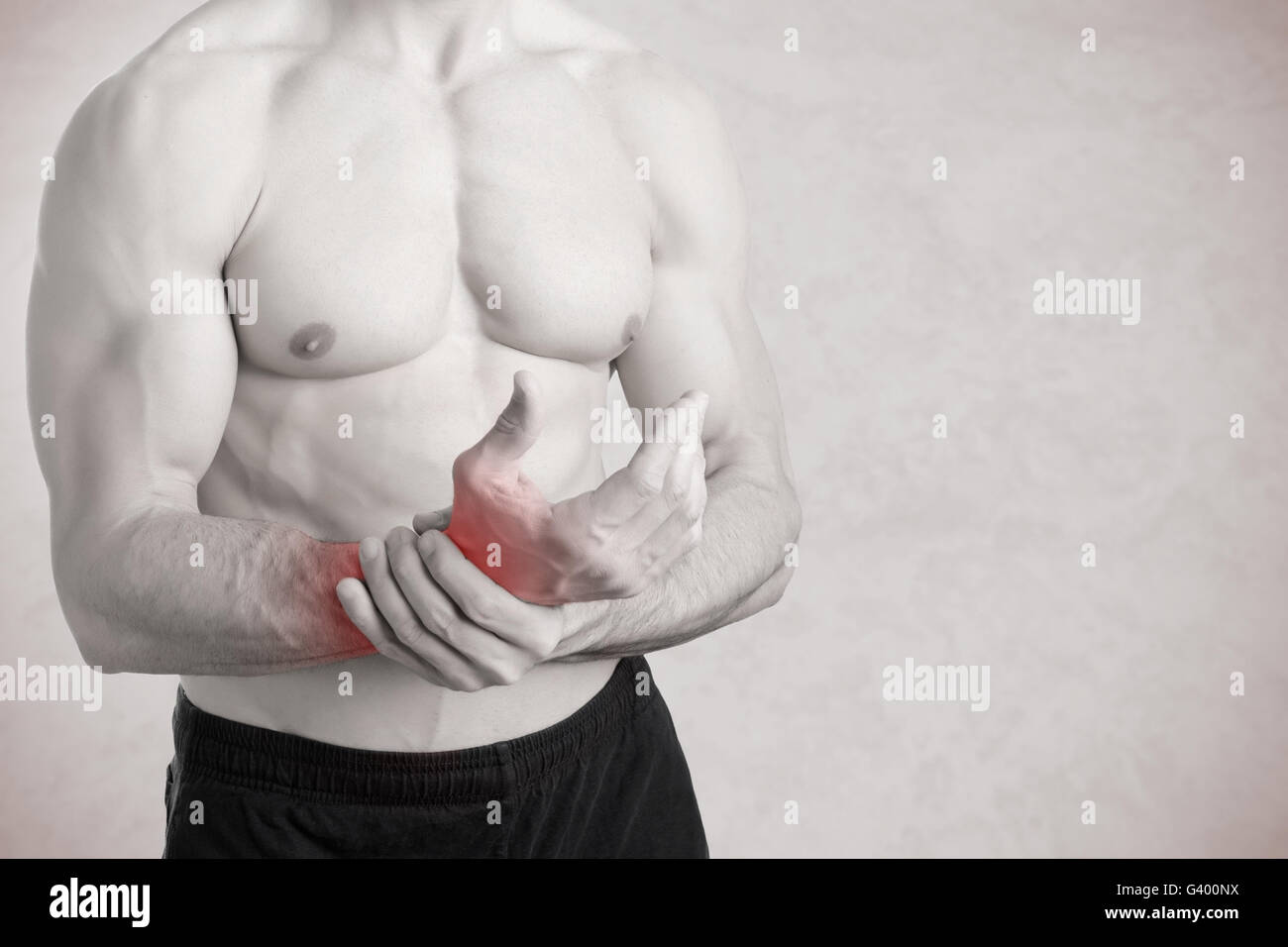 Male with pain in his wrist, isolated in a grey background, black and white, red around the paintful area - Stock Image
