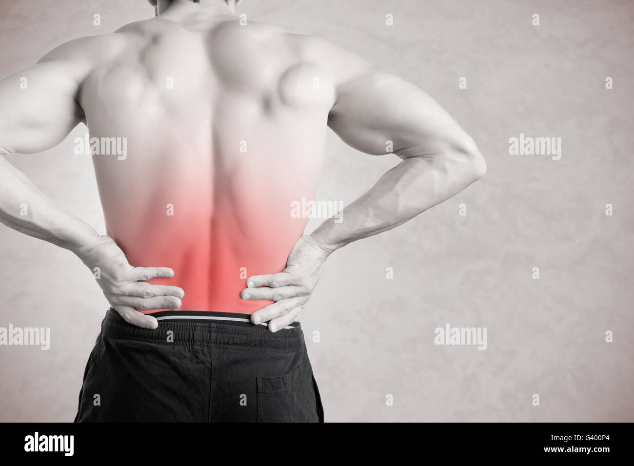 Male athlete with pain in his lower back, isolated in grey. Red spot around painful area. - Stock Image