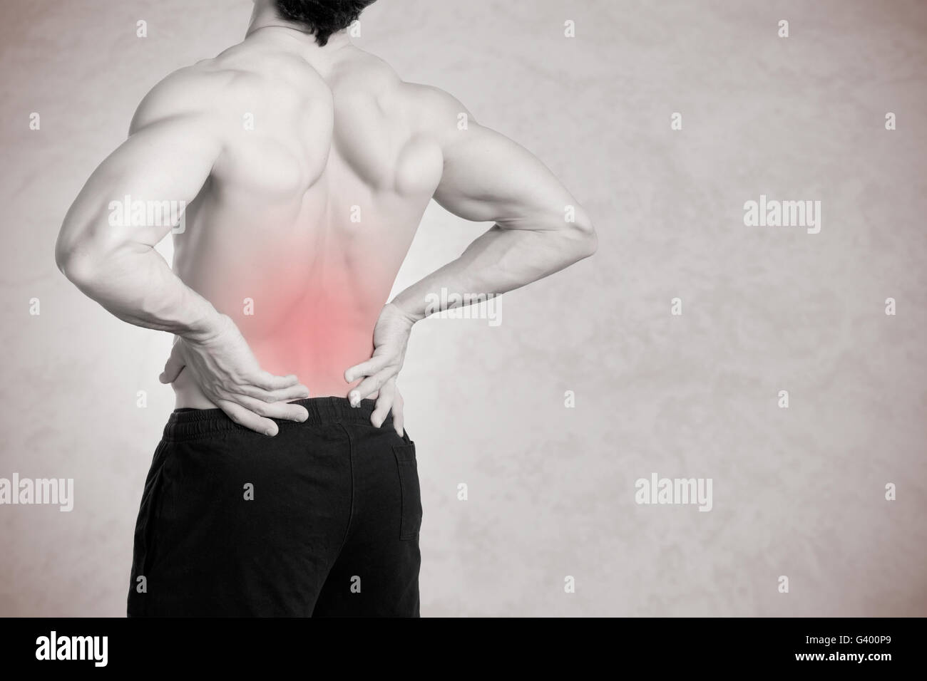 Male athlete with pain in his lower back, isolated in grey - Stock Image