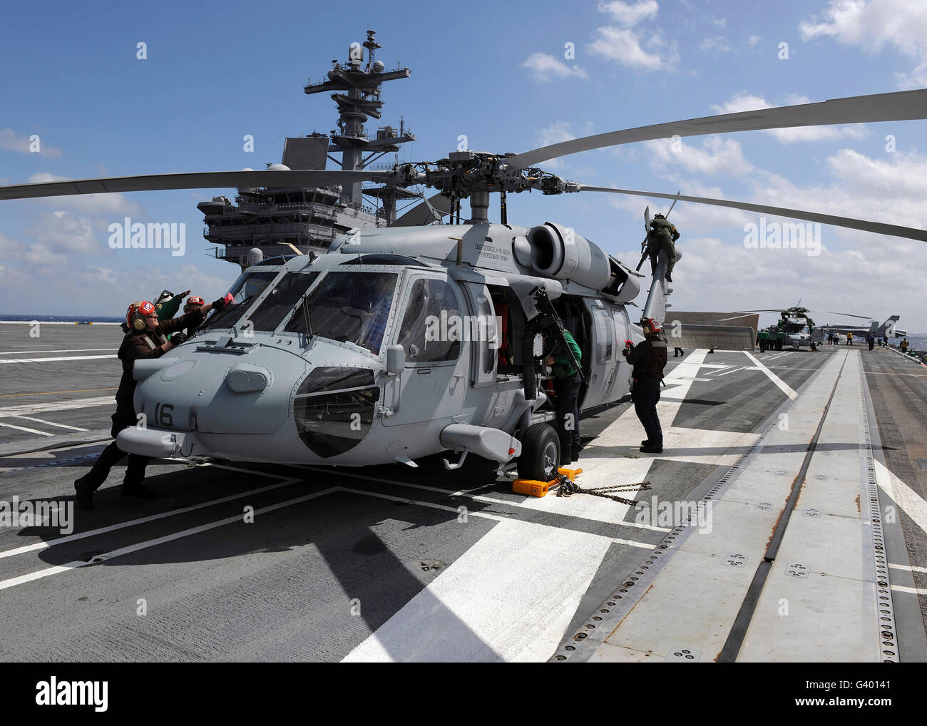Crewmen prepare an MH-60S Sea Hawk helicopter aboard USS George H.W. Bush. - Stock Image