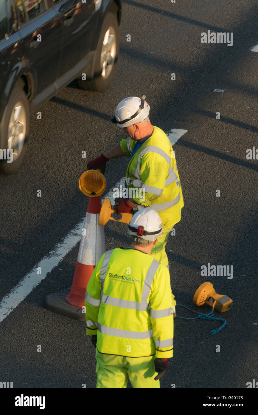 Workers putting out traffic cones on urban motorway,Glasgow,Scotland,UK, - Stock Image