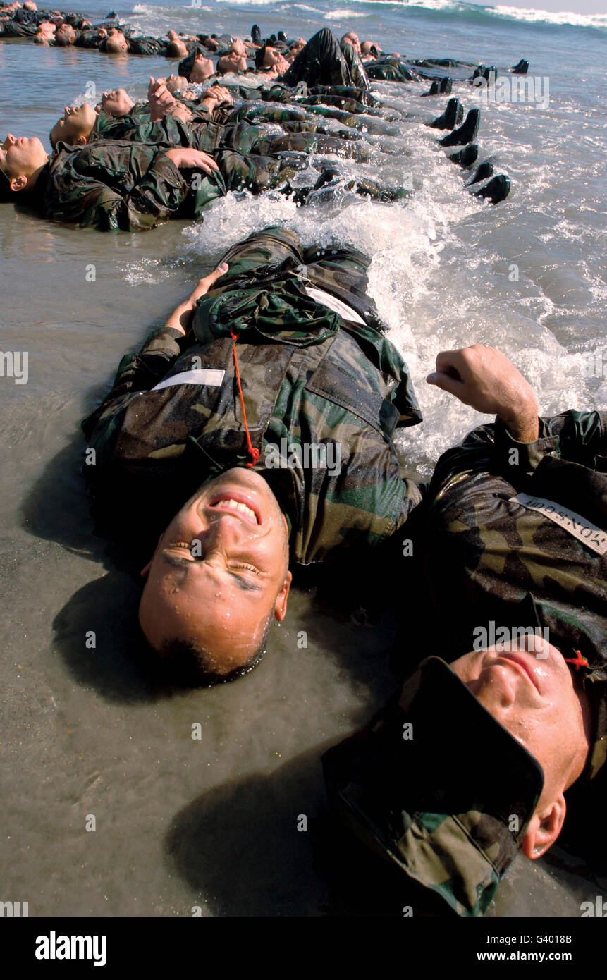 Soldiers in training lay in the surf as the frigid water rolls over them. - Stock Image