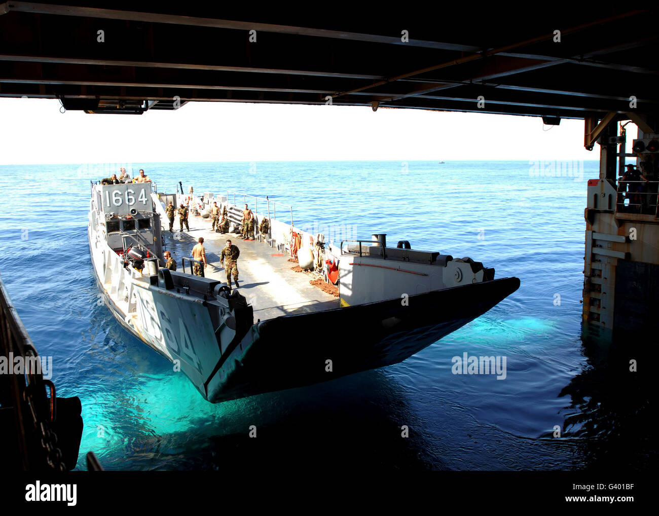 A landing craft utility departs the amphibious dock landing ship USS Fort McHenry. - Stock Image