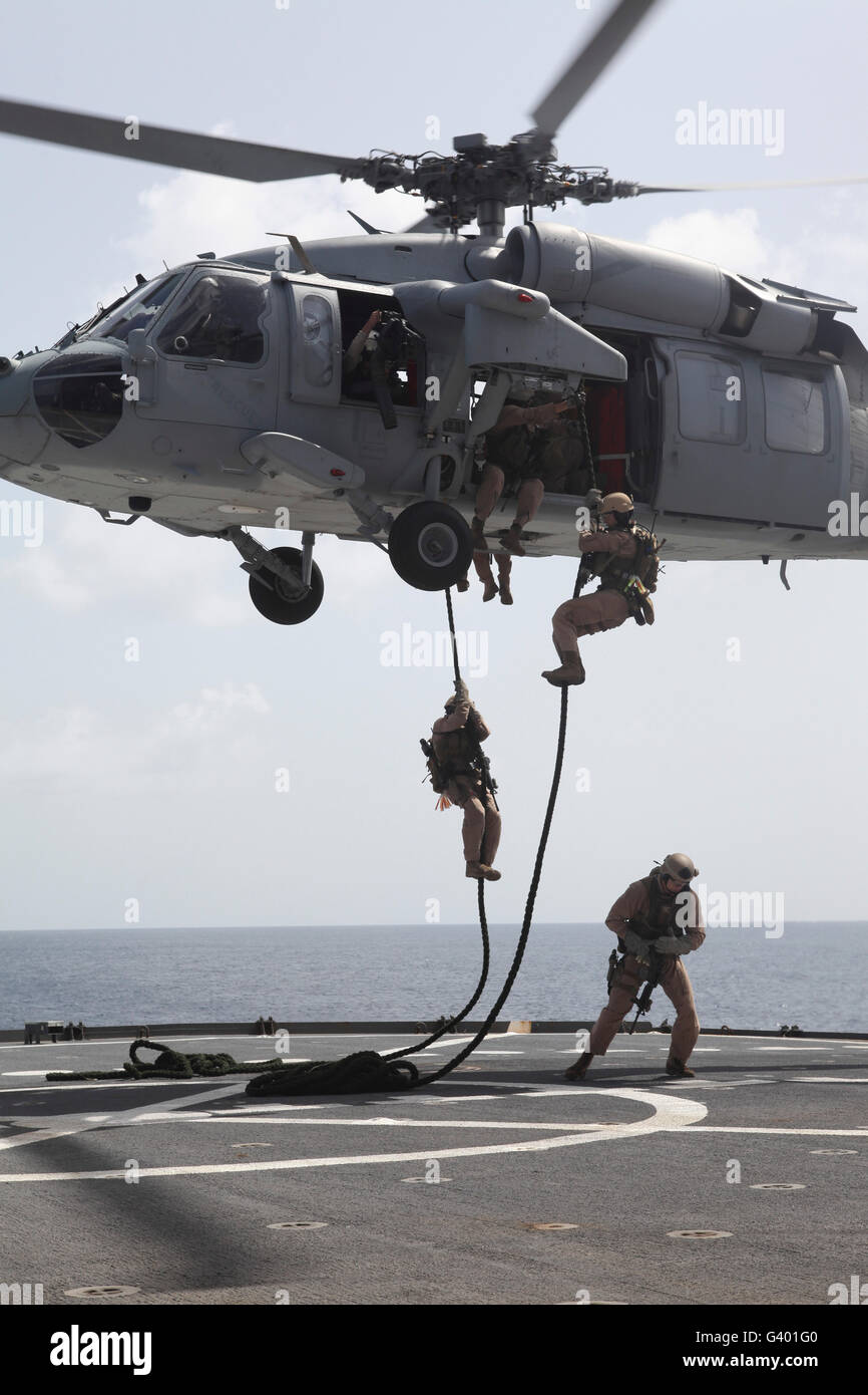 Marines fast-rope from an MH-60S Sea Hawk helicopter. - Stock Image