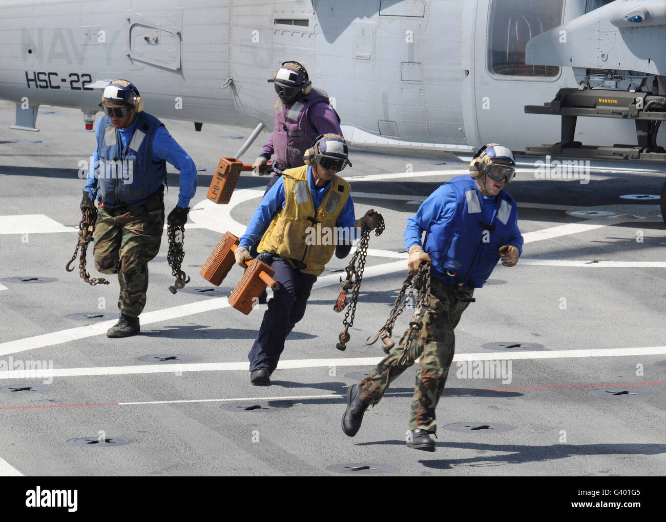 Sailors remove the chocks and chains from an MH-60S Sea Hawk helicopter. - Stock Image