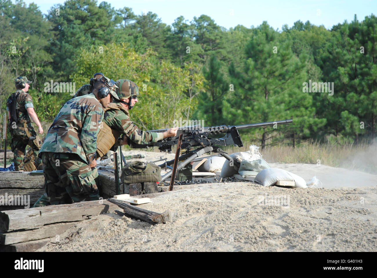 A soldier charges a .50-caliber machine gun on the firing range. - Stock Image