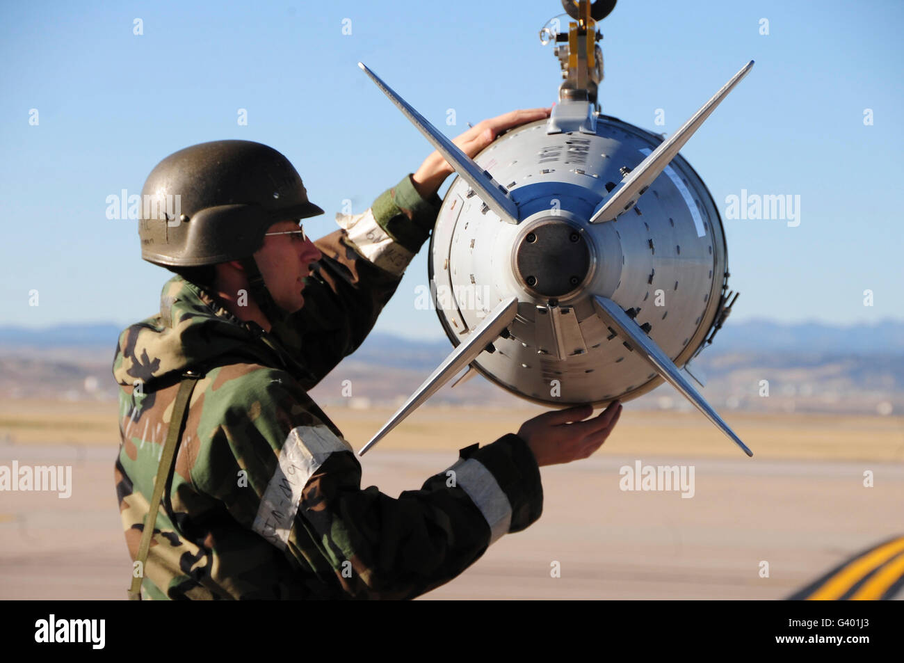 An Airman ensures a GBU-31 joint direct attack munition is secured to a bomb lift. - Stock Image