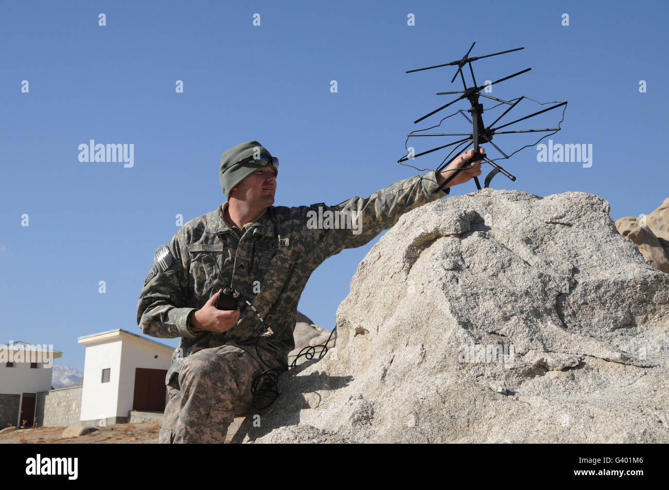U.S. Army soldier sets up a tactical satellite. - Stock Image