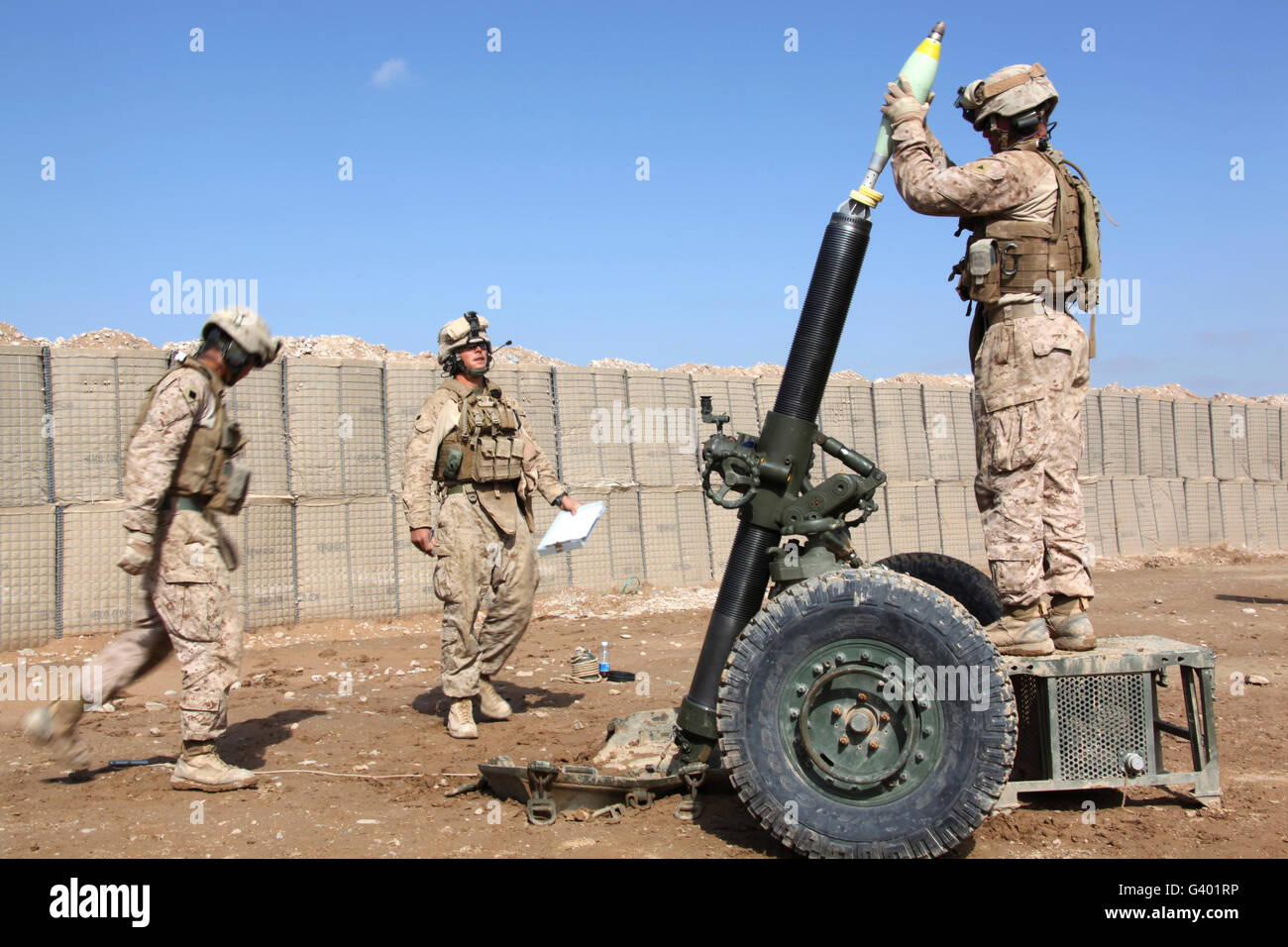Marines prepare to fire a 120mm mortar.