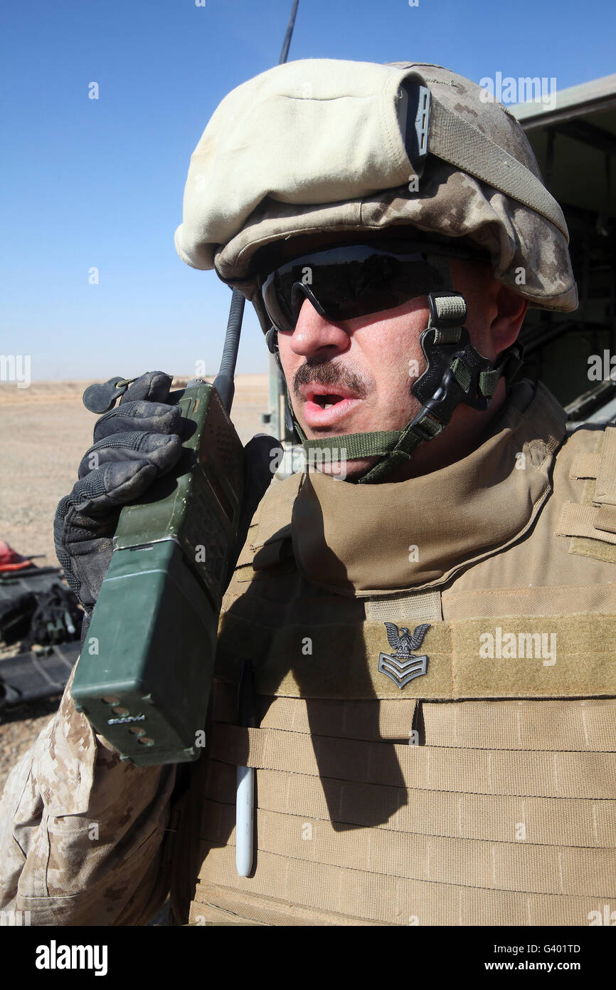 An officer relays commands on his walkie talkie. - Stock Image