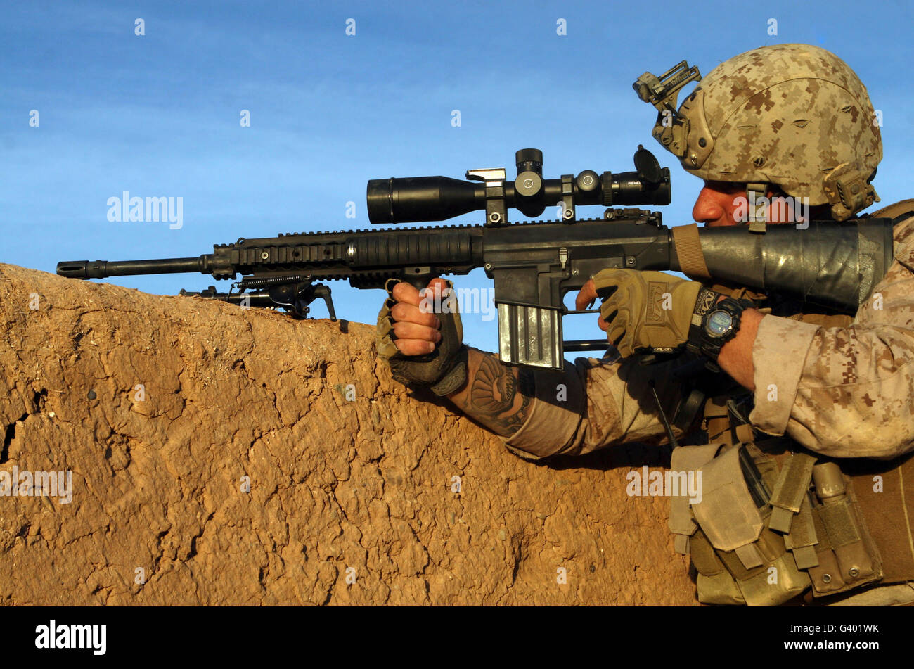 A sniper takes aim at insurgents during a firefight in Afghanistan. Stock Photo