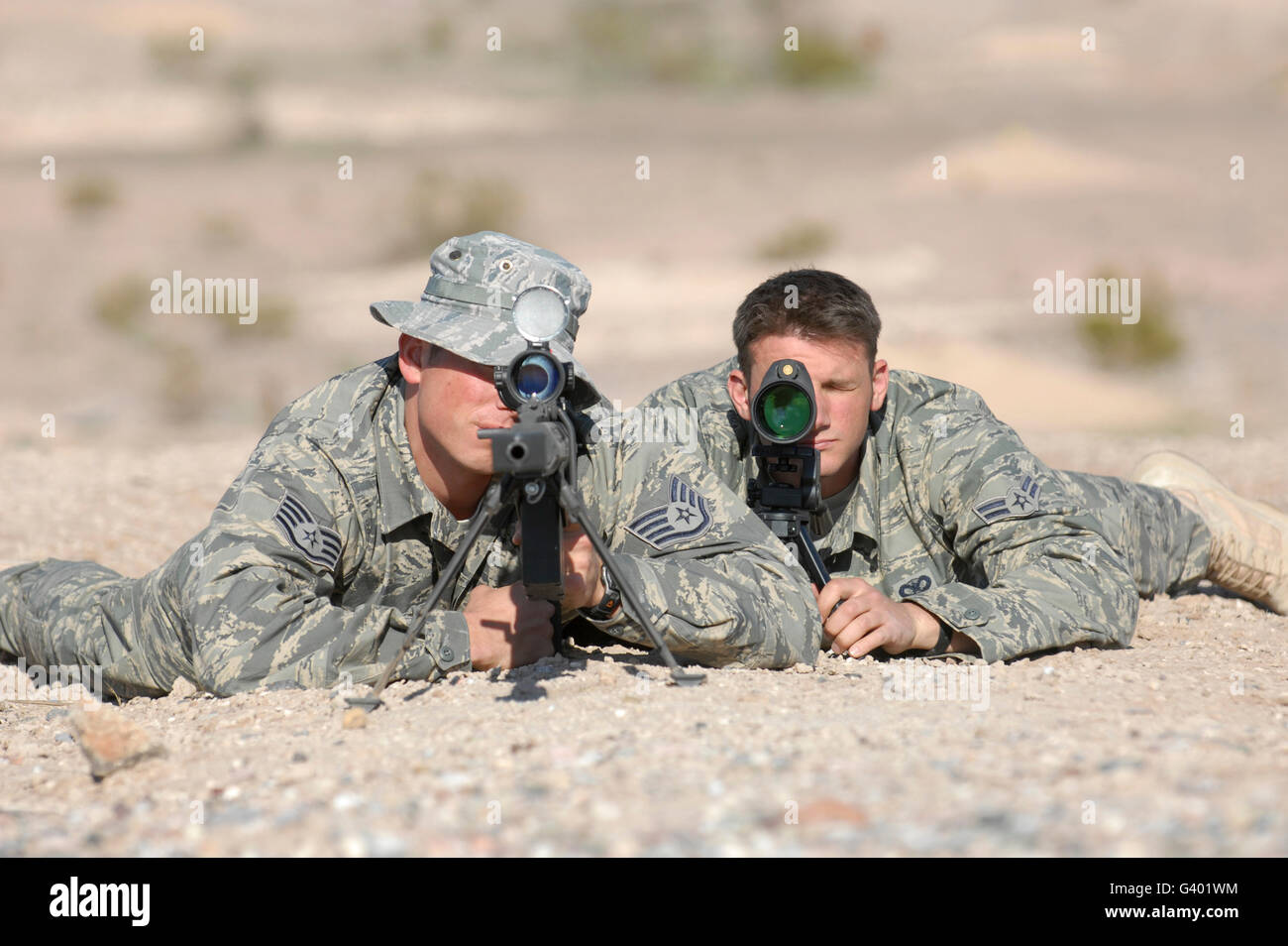 Soldiers look through the scope of their Barret M107 .50 caliber sniper rifles. - Stock Image