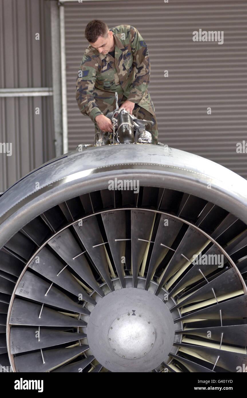 Airman checks components atop a C-5 Galaxy turbofan engine. - Stock Image