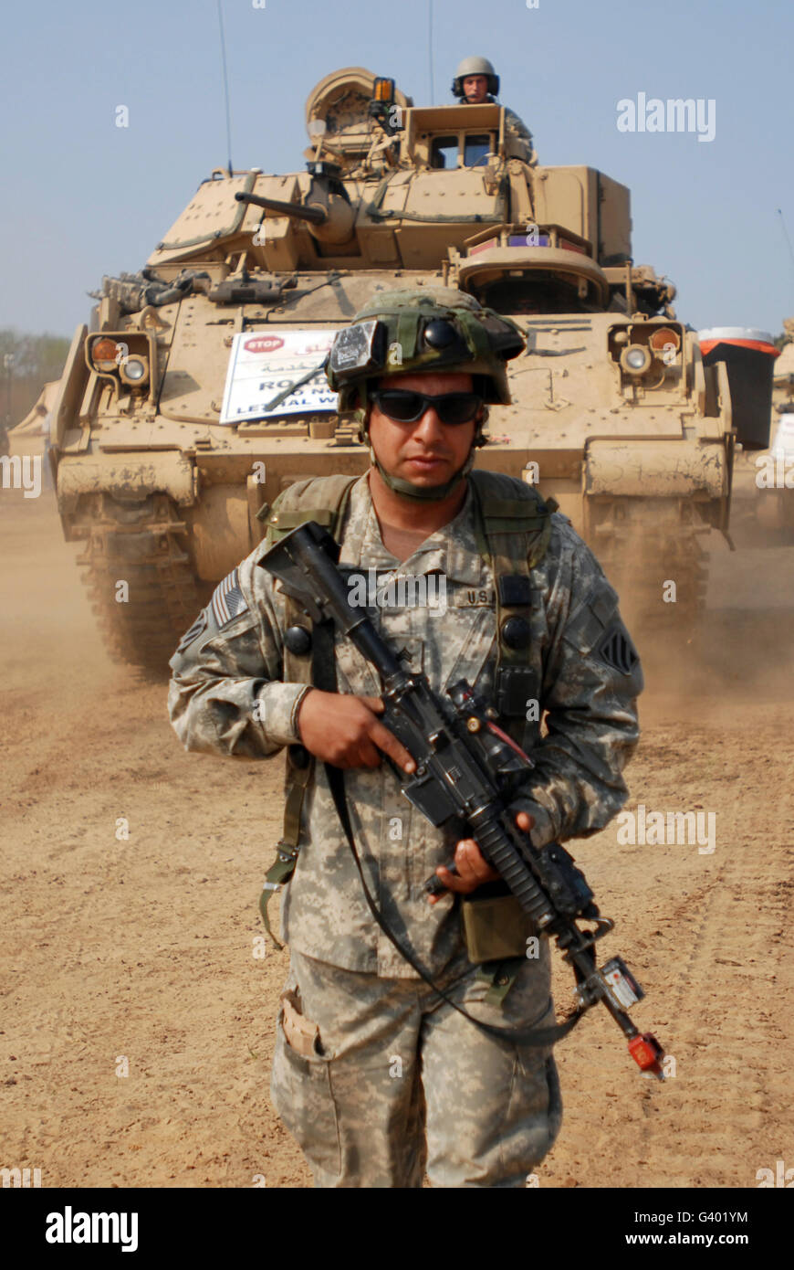 U.S. Army Sergeant ground guides an M2 Bradley Fighting Vehicle. - Stock Image
