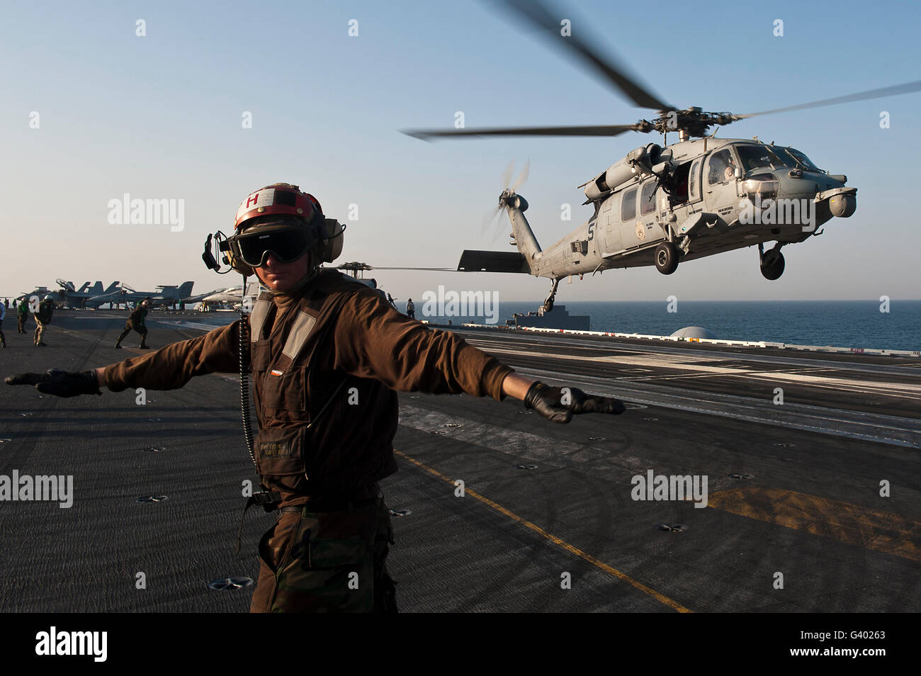 Airman checks for a clear deck as an MH-60S Sea Hawk takes off USS John C. Stennis. - Stock Image