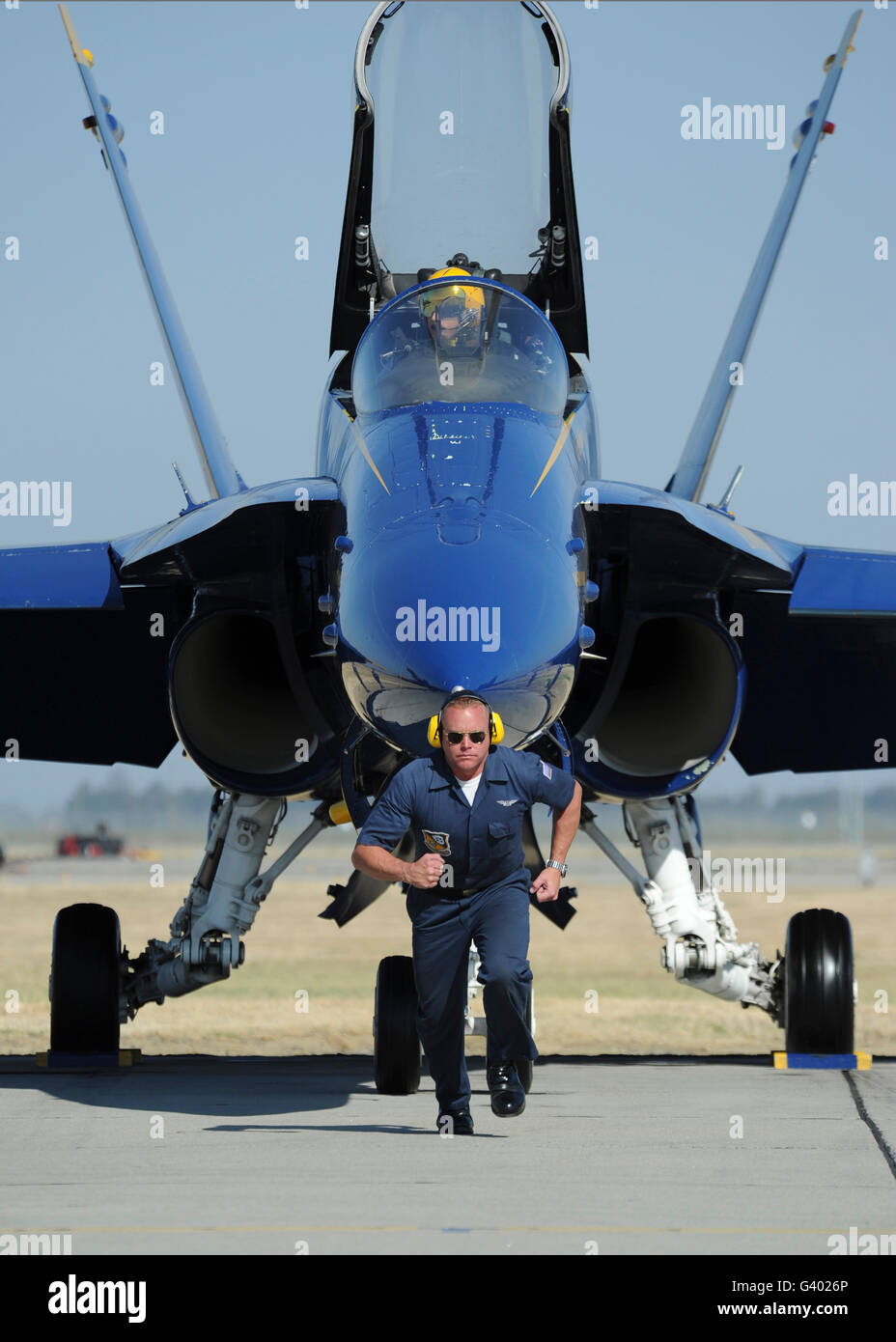 A crew chief sprints ahead of a Blue Angels F/A-18 aircraft. - Stock Image