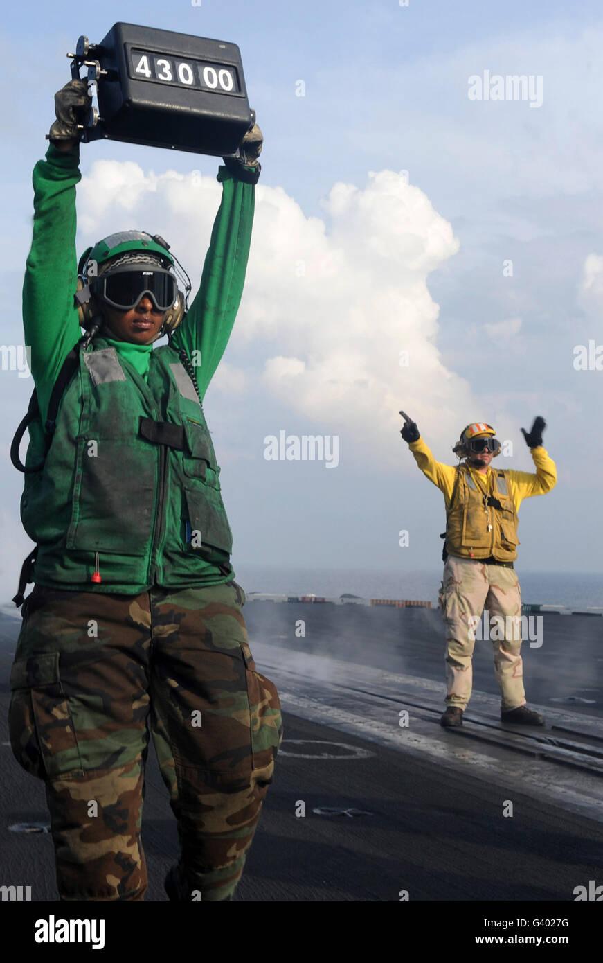 Airmen communicate to aircraft aboard the flight deck of USS John C. Stennis. - Stock Image