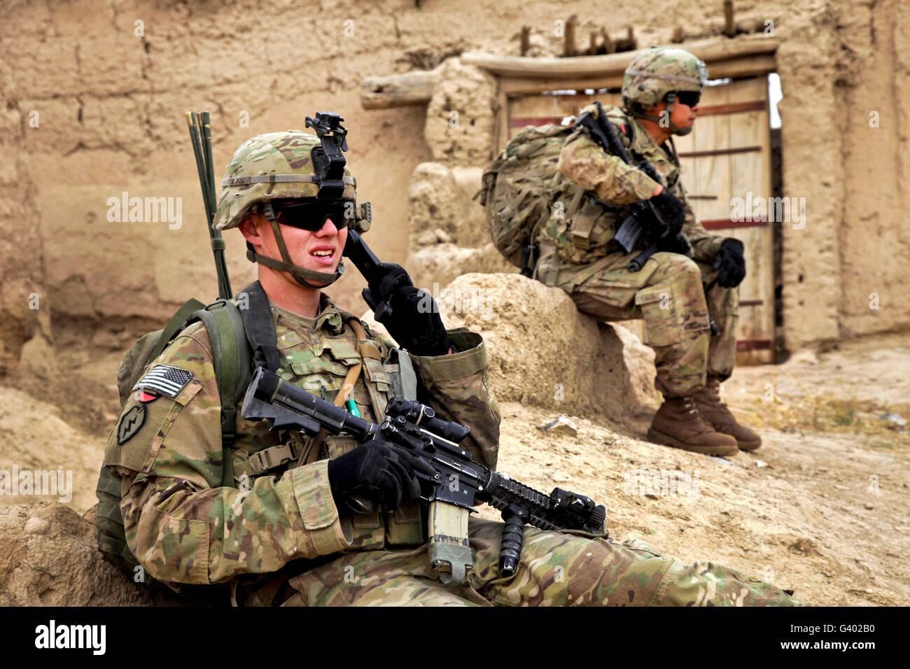 A soldier calls in description of person of interest to higher ups. - Stock Image