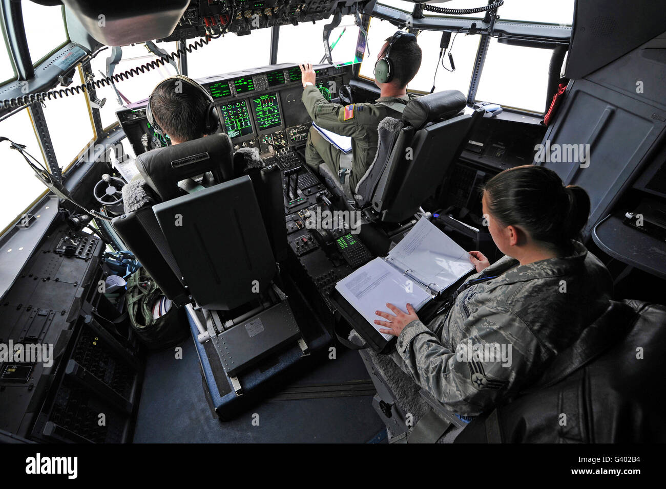 Aircrew perform preflight checklists in a C-130J Super Hercules before takeoff. - Stock Image