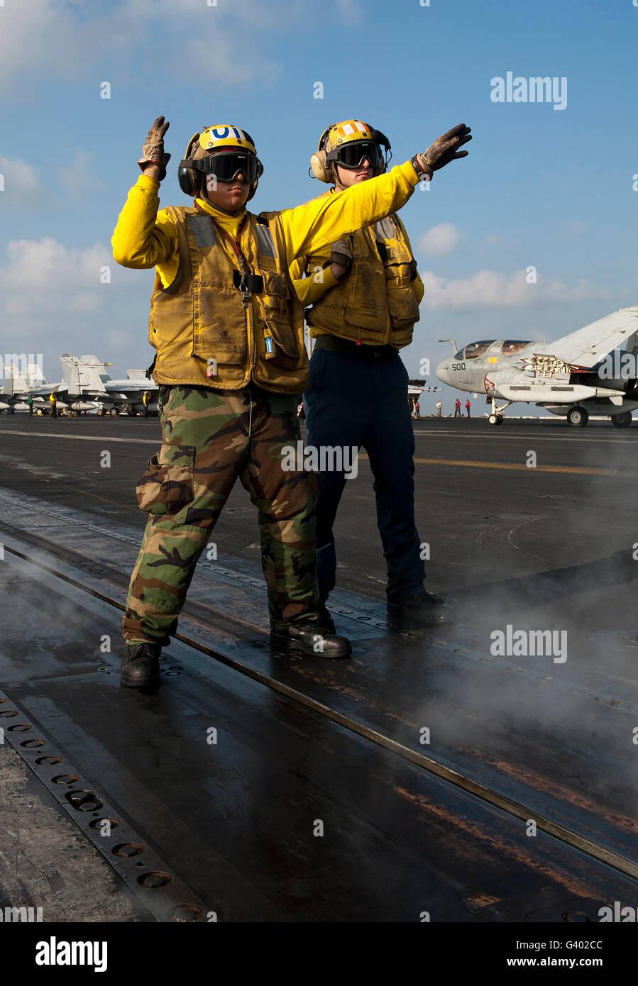 Airmen direct an F/A-18C Hornet on the flight deck of USS John C. Stennis. - Stock Image